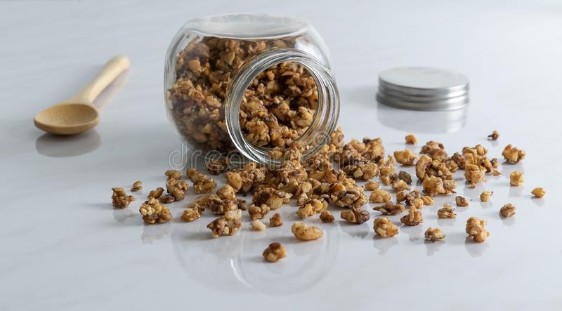 Eigengemaakte gezonde en voedzame ontbijtgranola in een glaskruik met houten lepel op schone witte marmeren keukenlijst royalty-vrije stock afbeeldingen