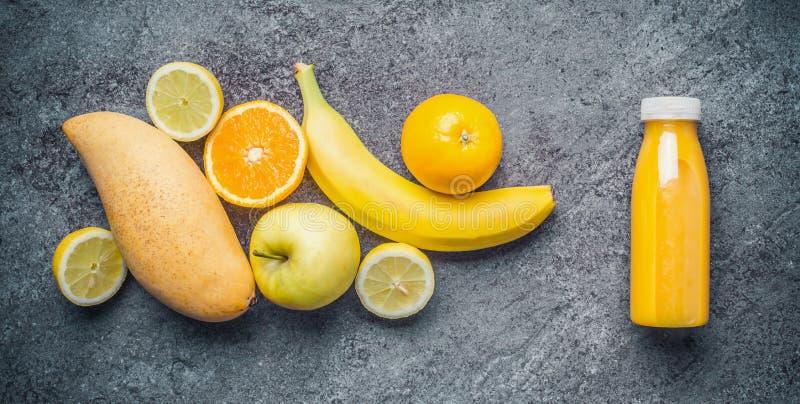 Eigengemaakte gezonde verfrissende fruitdrank in fles met ingrediënten Gele citrusvrucht en vruchten smoothie, sappige vitaminedr stock foto