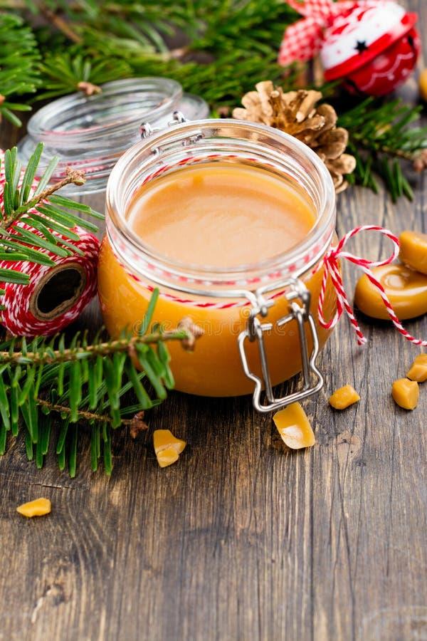 Eigengemaakte gezouten karamelsaus in een glaskruik en Kerstmisdecor op houten achtergrond stock fotografie