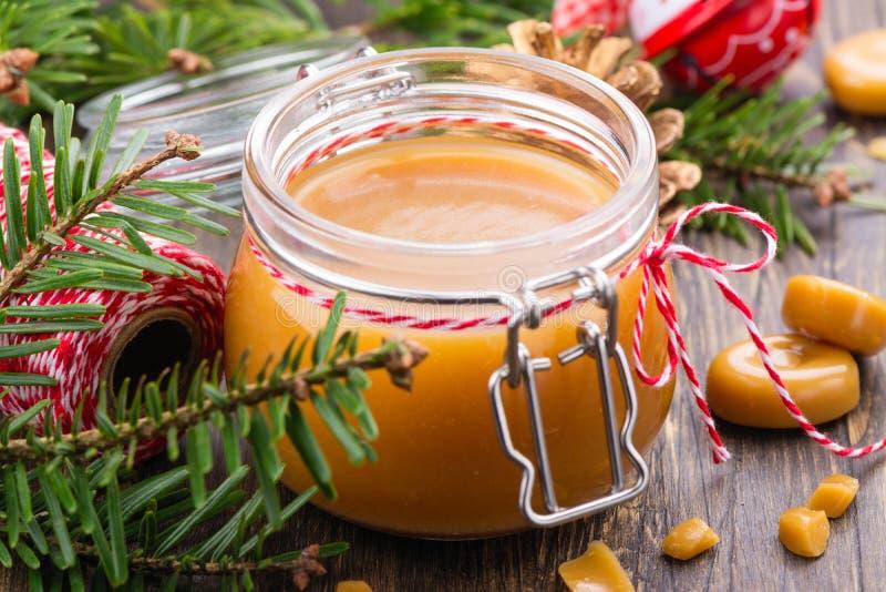 Eigengemaakte gezouten karamelsaus in een glaskruik en Kerstmisdecor op houten achtergrond royalty-vrije stock fotografie