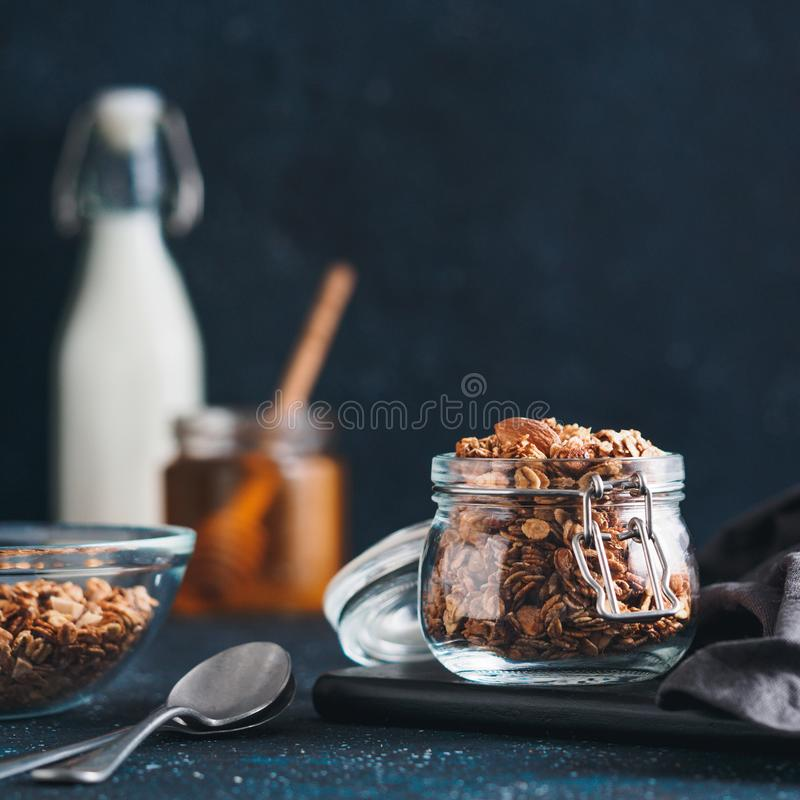 Eigengemaakte granola in glaskruik op donkere lijst stock afbeelding