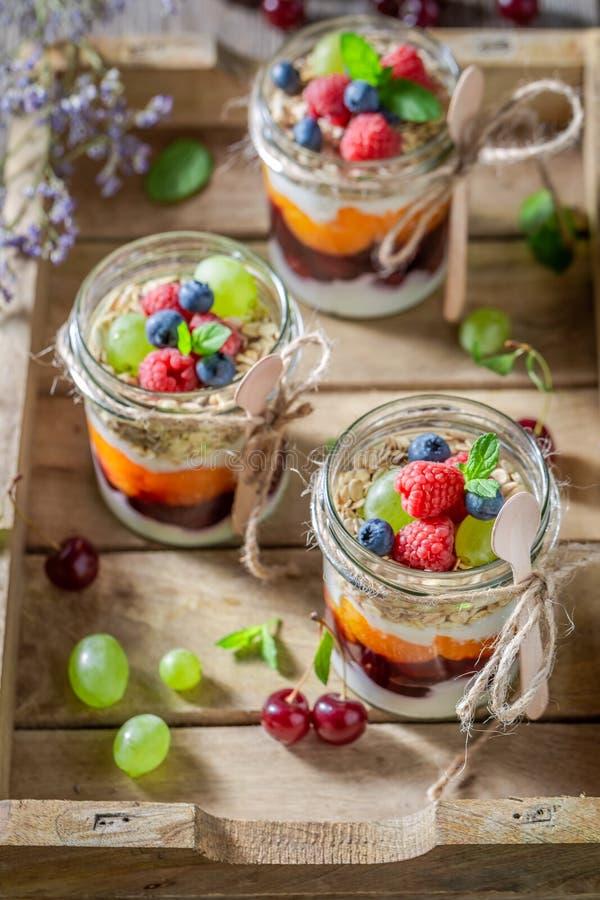 Eigengemaakte granola met verse bessen en yoghurt in kruik stock foto's