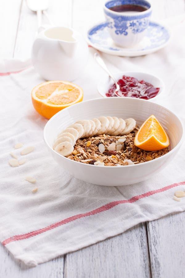 Eigengemaakte granola met verse vruchten in een witte kom met jam, melk en koffie op een houten achtergrond voor ontbijt royalty-vrije stock afbeeldingen