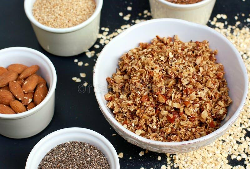 Eigengemaakte granola in witte kom met amandel en zaden op zwarte achtergrond royalty-vrije stock afbeelding