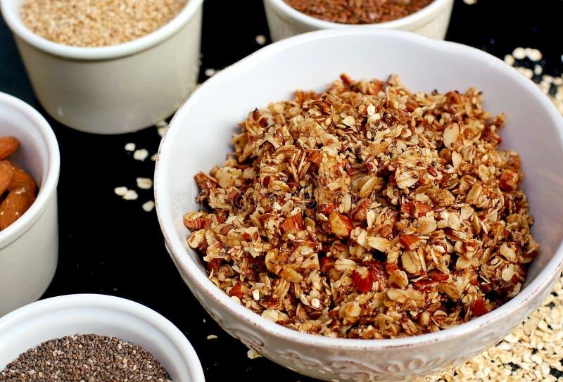Eigengemaakte granola in witte kom met amandel en zaden op zwarte achtergrond stock foto