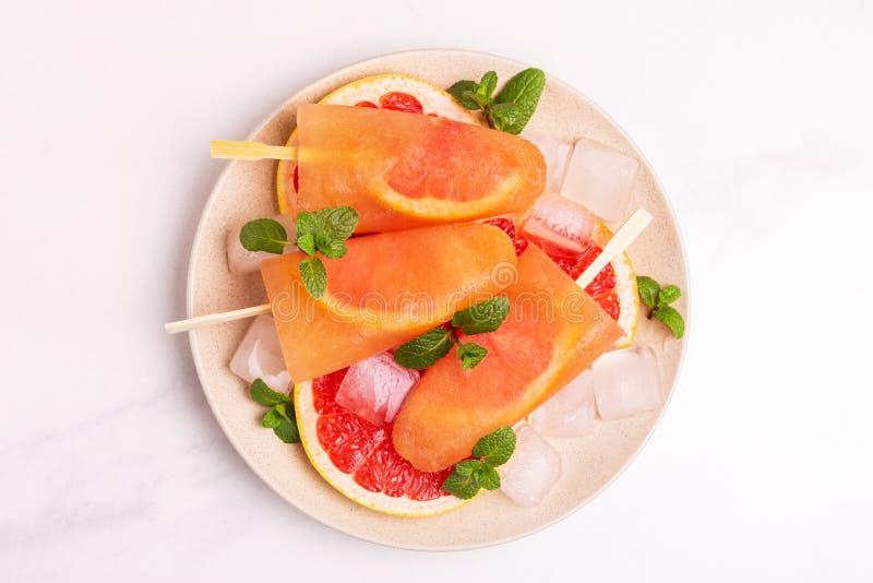 Eigengemaakte grapefruitijslolly met rijpe grapefruitplakken en verse munt stock foto's