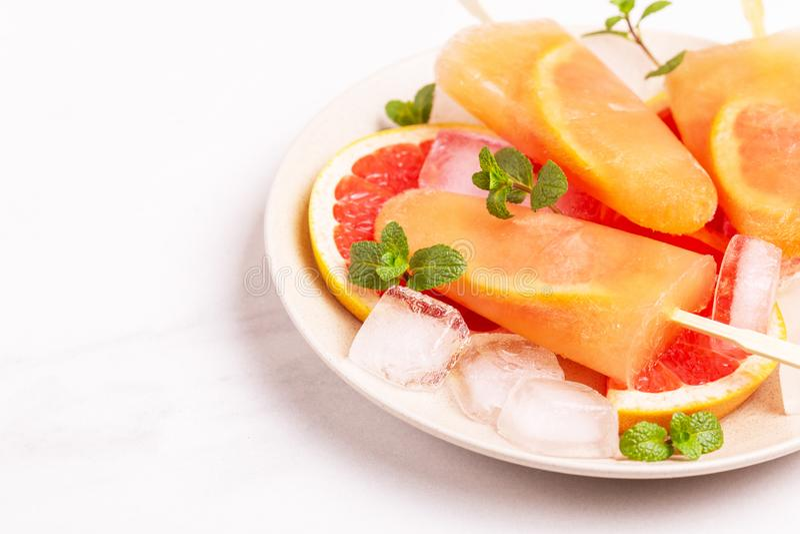 Eigengemaakte grapefruitijslolly met rijpe grapefruitplakken en verse munt stock fotografie