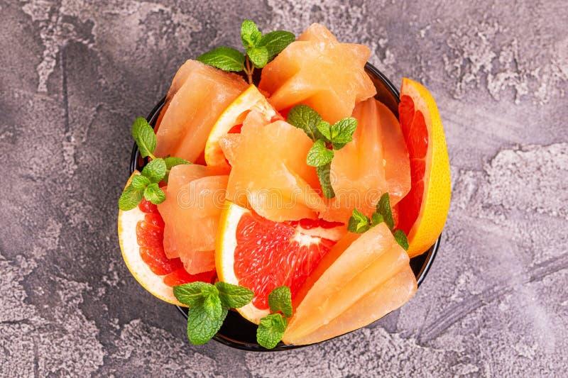 Eigengemaakte grapefruitijslolly met rijpe grapefruitplakken en verse munt royalty-vrije stock afbeelding