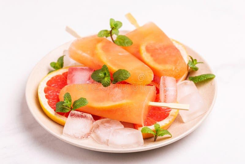 Eigengemaakte grapefruitijslolly met rijpe grapefruitplakken en verse munt stock afbeeldingen