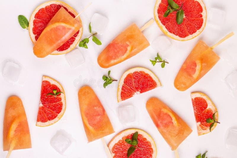 Eigengemaakte grapefruitijslolly met rijpe grapefruitplakken en verse munt stock foto