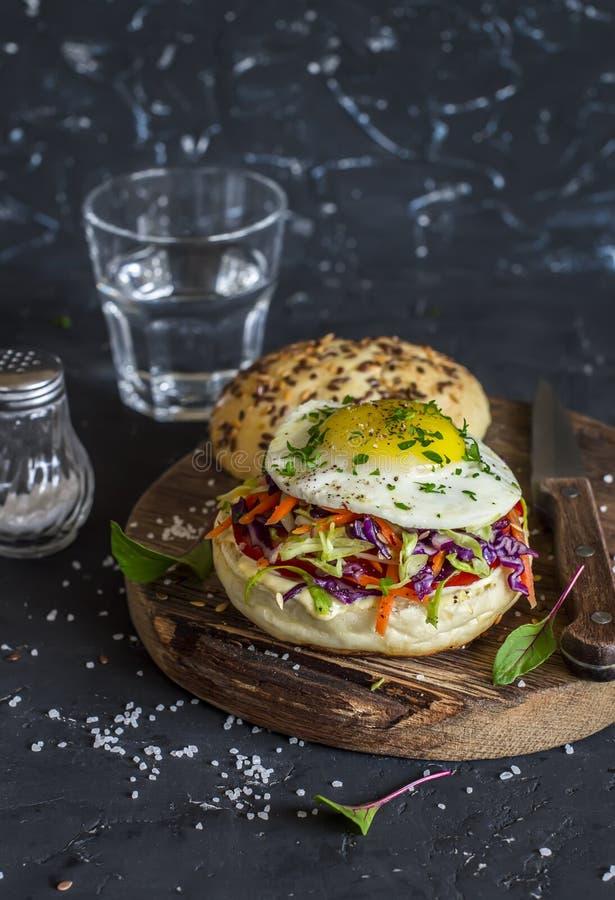 Eigengemaakte hamburger met gebraden ei en koolsla op rustieke houten raad op een donkere steenachtergrond stock foto's
