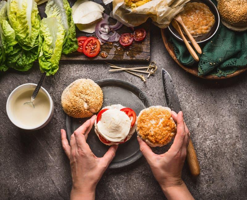 Eigengemaakte Hamburger Vrouwelijke vrouwenhanden die hamburger op de achtergrond van de keukenlijst met ingrediënten maken stock foto