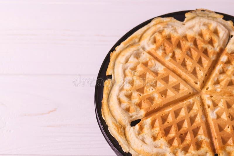 Eigengemaakte hart gevormde wafels in de pan van de ijzerwafel stock fotografie