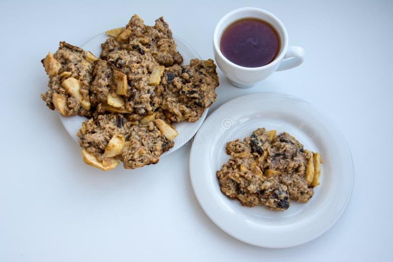 Eigengemaakte havermeelkoekjes op plaat met GLB van thee stock afbeelding
