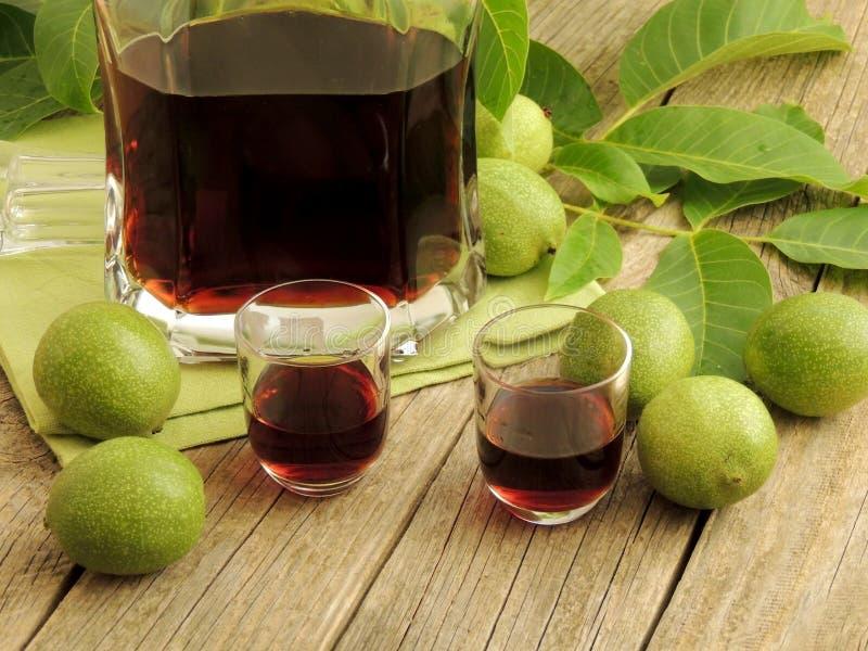 Eigengemaakte Italiaanse nocinolikeur met onrijpe groene noten en alcohol stock afbeelding