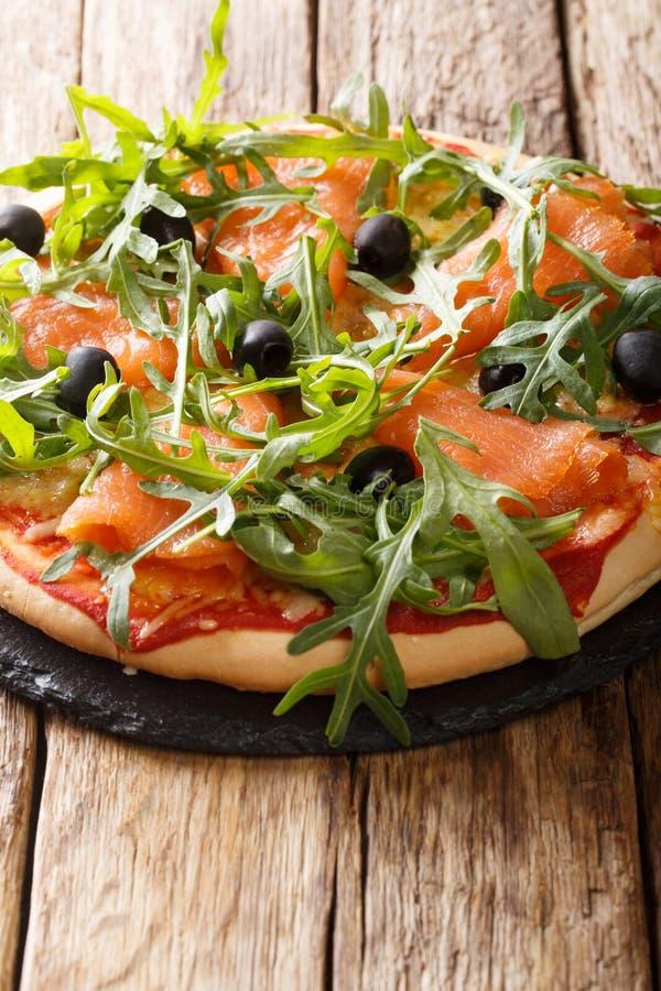Eigengemaakte Italiaanse pizza met gezouten zalm, verse arugula, olijven en kaasclose-up verticaal royalty-vrije stock afbeelding