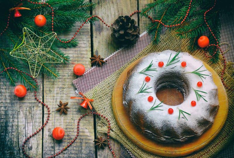 Eigengemaakte Kerstmiscake met Amerikaanse veenbes en nieuw de decoratiekader van de jaarboom op houten lijstachtergrond Rustieke royalty-vrije stock afbeelding