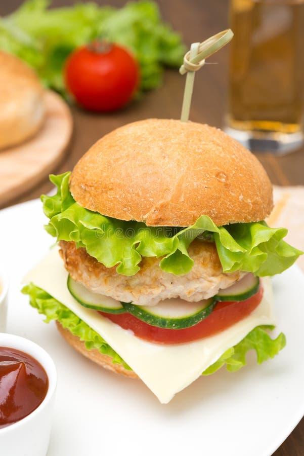 Eigengemaakte kippenhamburger met ketchup en mosterd op een plaat stock foto