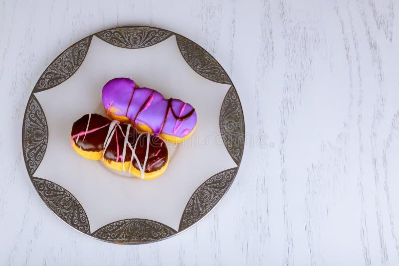 eigengemaakte kleurrijke donuts met chocolade en suikerglazuurglans op houten achtergrond stock foto's