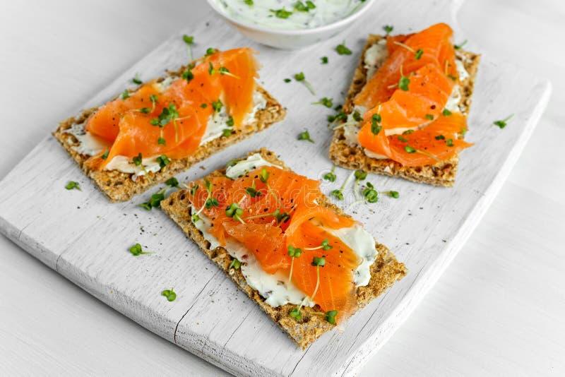 Eigengemaakte Knäckebroodtoost met Gerookte Zalm, Gesmolten Kaas en tuinkerssalade op witte houten raad royalty-vrije stock foto's
