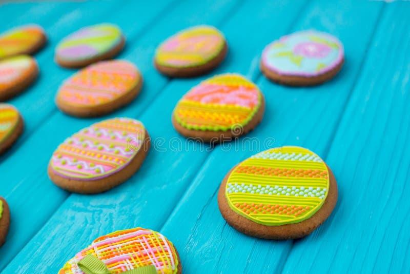 Eigengemaakte koekjes met suikerglazuur in de vorm van een ei voor Pasen Heerlijke Pasen-koekjes op een blauwe achtergrond Cooki royalty-vrije stock foto