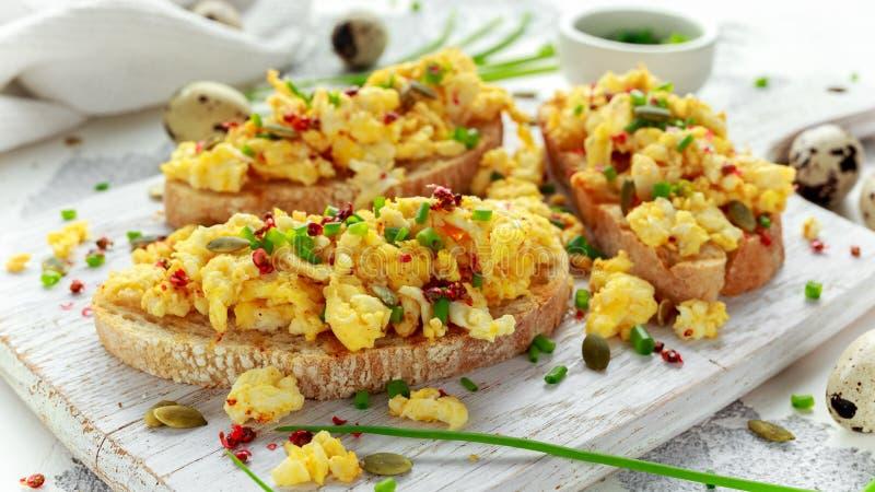 Eigengemaakte Kwartelsroereieren op knapperige toost, brood met groene ui, bieslook op witte raad stock fotografie