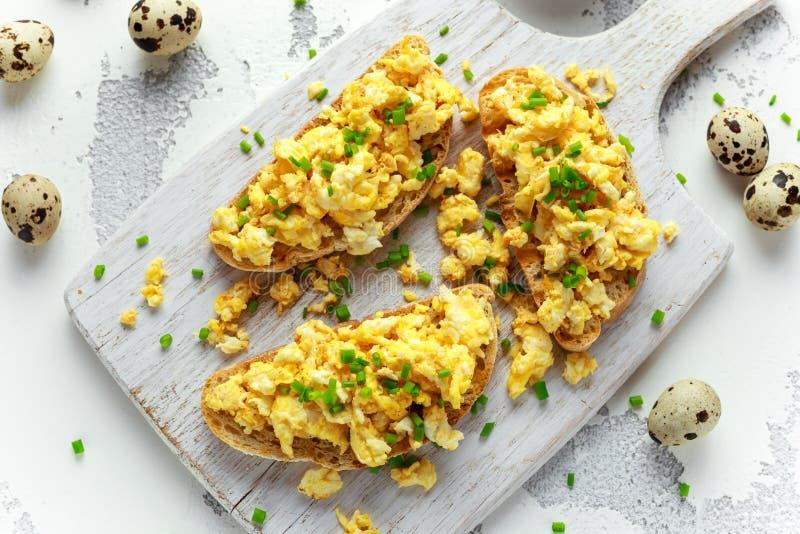 Eigengemaakte Kwartelsroereieren op knapperige toost, brood met groene ui, bieslook op witte raad stock foto's