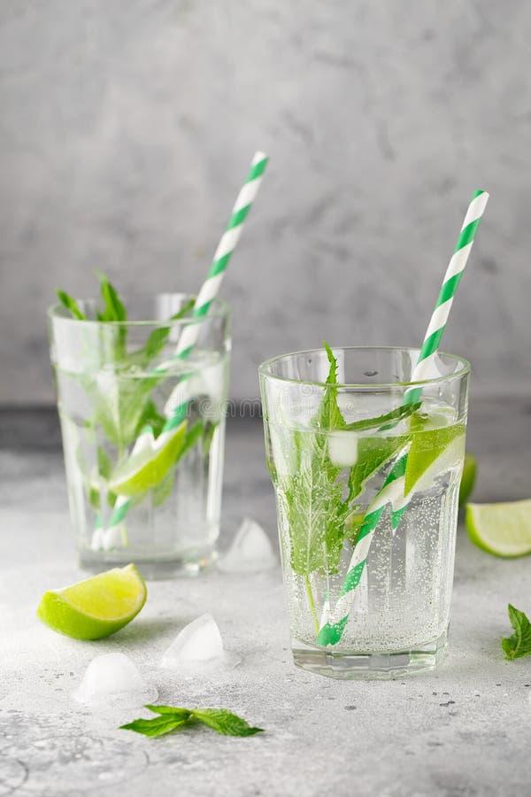 Eigengemaakte limonade met kalk, munt in een glas op een grijze concrete achtergrond Gezond Vers Muntwater met Kalk en ijs royalty-vrije stock foto's