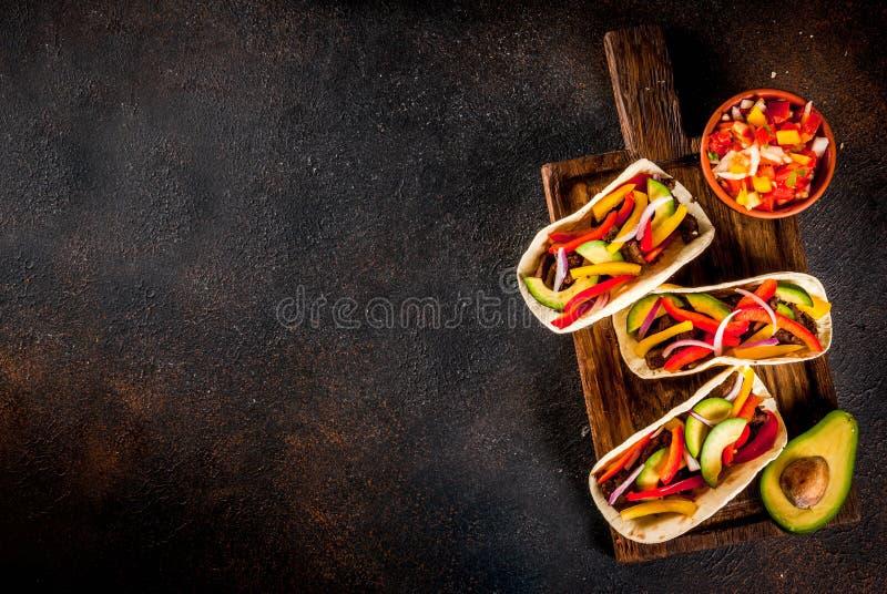 Eigengemaakte Mexicaanse varkensvleestaco's met groenten en salsa, op donker r royalty-vrije stock foto's
