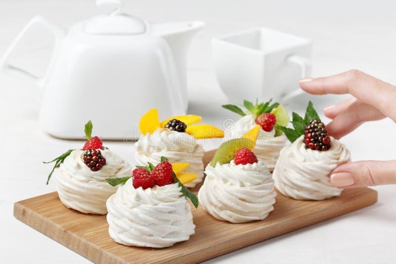 Eigengemaakte minipavlovacakes met slagroom en verse bessen stock afbeelding