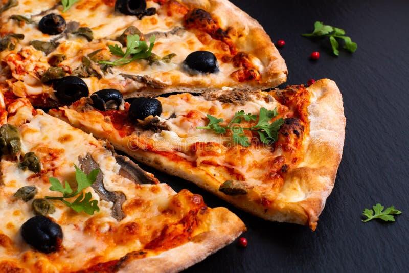 Eigengemaakte Napoli-Pizza of ansjovissenpizza op zwarte leisteen stock afbeeldingen