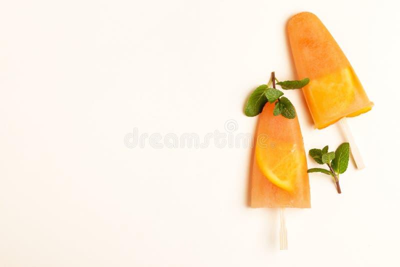Eigengemaakte oranje sorbet met oranje plakken binnen en verse munt stock afbeeldingen