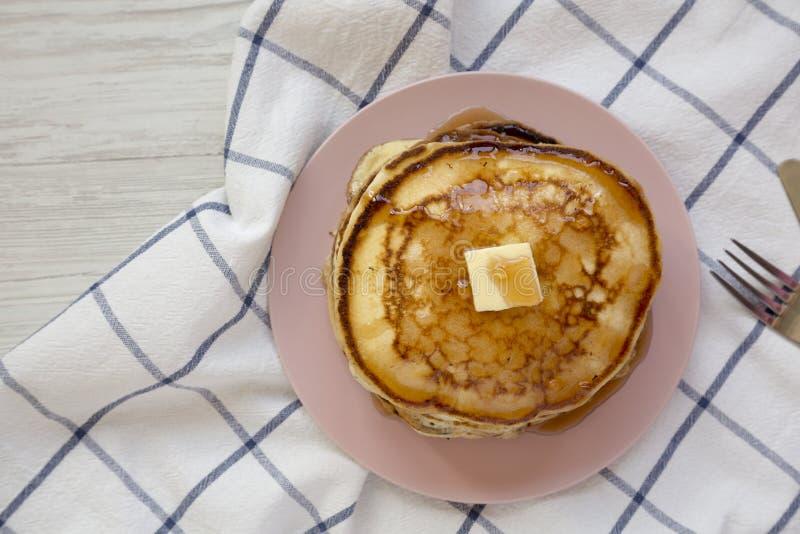 Eigengemaakte pannekoeken met boter en ahornstroop op een roze plaat, hoogste mening Close-up stock foto
