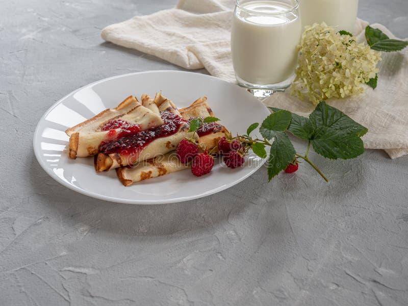 Eigengemaakte pannekoeken met frambozenjam, natuurlijke melk stock foto