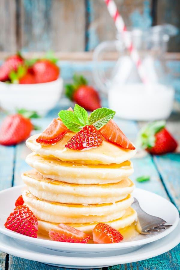 Eigengemaakte pannekoeken met honing en aardbeien stock fotografie