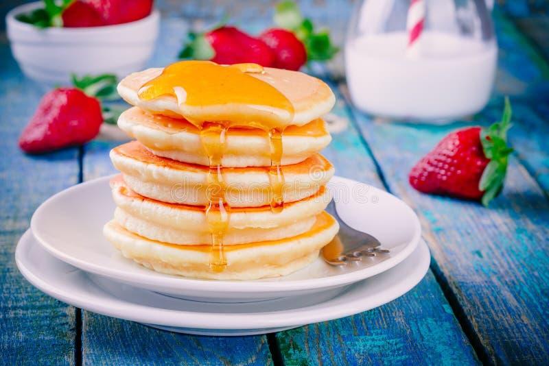 Eigengemaakte pannekoeken met honing en aardbeien royalty-vrije stock afbeeldingen