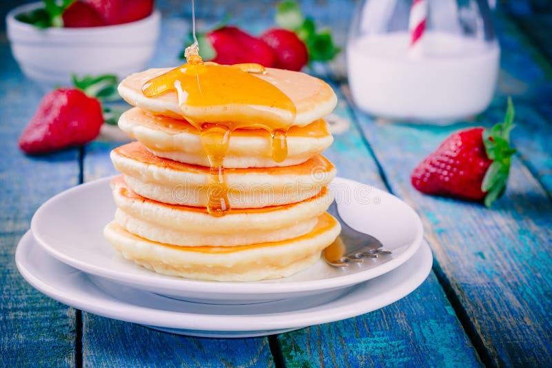 Eigengemaakte pannekoeken met honing en aardbeien royalty-vrije stock fotografie