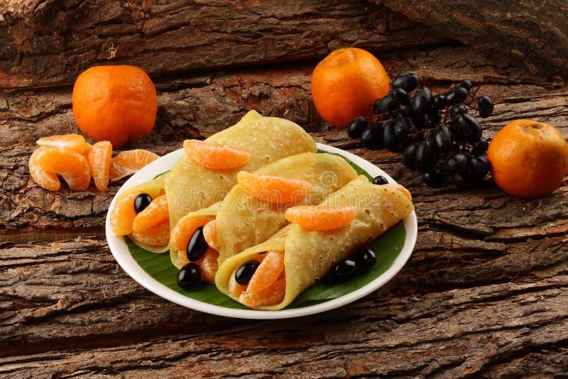 Eigengemaakte Pannekoeken met verse organische vruchten en honing stock afbeelding