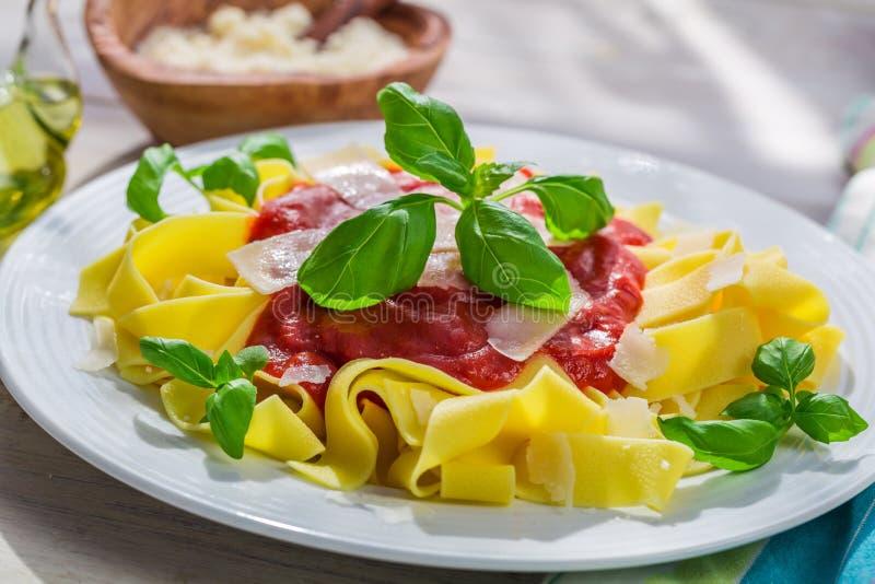 Eigengemaakte pappardelledeegwaren met tomatensaus en basilicum royalty-vrije stock fotografie