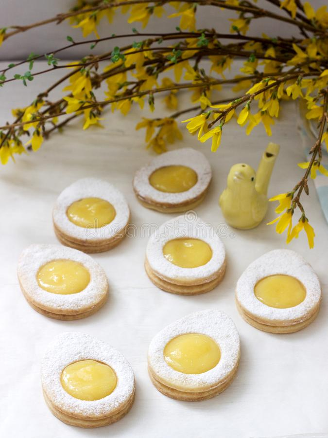 Eigengemaakte Pasen-citroenkoekjes en forsythia bloeiende takjes op een lichte achtergrond stock afbeeldingen
