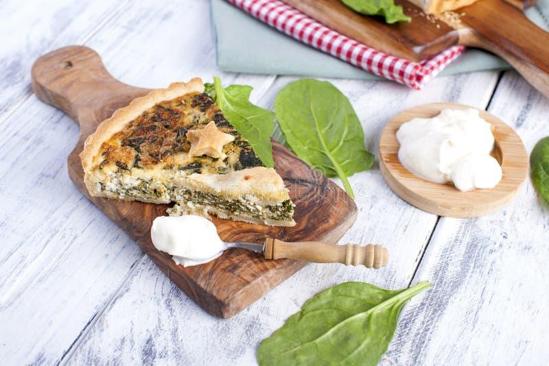 Eigengemaakte pastei met spinazie en kaas, op een witte houten achtergrond het dienen van pastei royalty-vrije stock fotografie