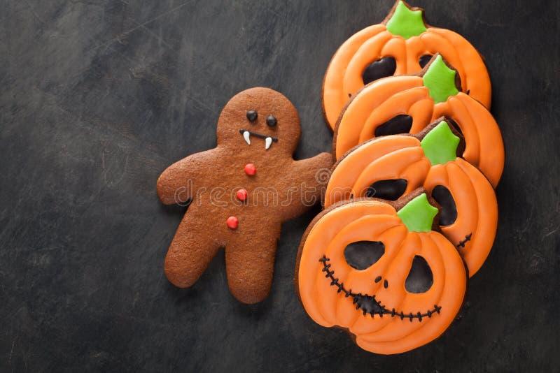 Eigengemaakte peperkoekkoekjes voor Halloween in de vorm van pompoenen en van peperkoekmensen vampier op donkere concrete achterg stock foto's