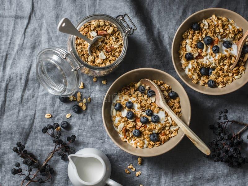 Eigengemaakte pindakaasgranola met Griekse yoghurt en bosbessen op een grijze achtergrond, hoogste mening Gezonde energieontbijt  royalty-vrije stock afbeeldingen