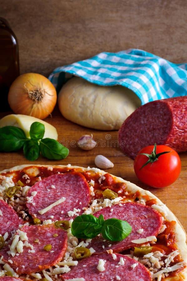 Eigengemaakte pizza en ingrediënten stock afbeeldingen