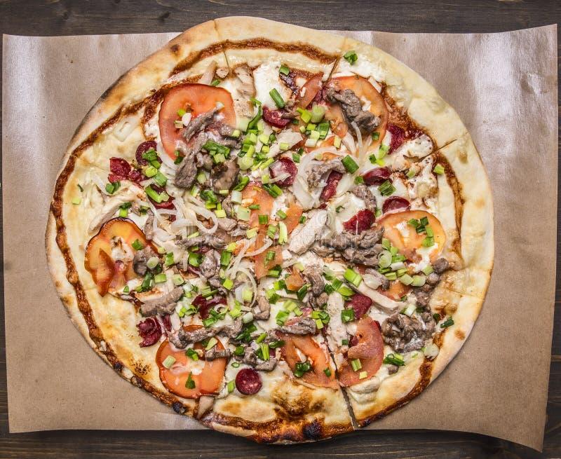 Eigengemaakte pizza met bacon, tomaat en kaas op bakseldocument op houten rustieke achtergrond hoogste menings dichte omhooggaand stock fotografie