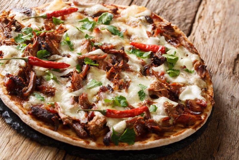 Eigengemaakte pizza met getrokken varkensvlees, kaas, peper en barbecuesausclose-up horizontale, rustieke stijl stock foto