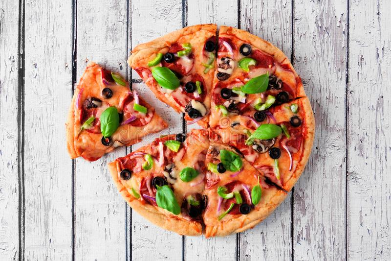 Eigengemaakte pizza met pepperonis, groenten en basilicum, hoogste mening met gesneden plakken over wit hout royalty-vrije stock afbeeldingen