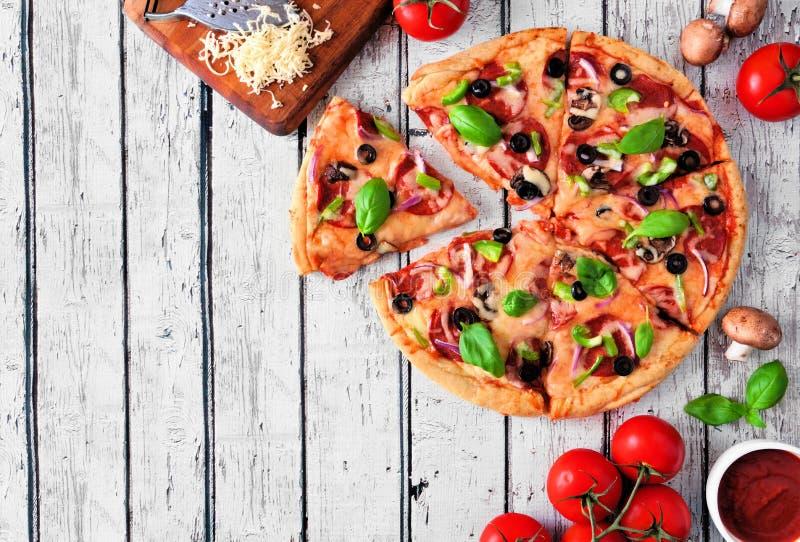 Eigengemaakte pizza met pepperonis, groenten en basilicum, hoogste mening, hoekgrens tegen een witte houten achtergrond met exemp stock foto's