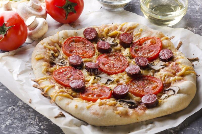 Eigengemaakte pizza met tomaten, vlees, paddestoelen en kaas, verse groenten, kom met olie op de ristic grijze lijst Close-up van stock foto
