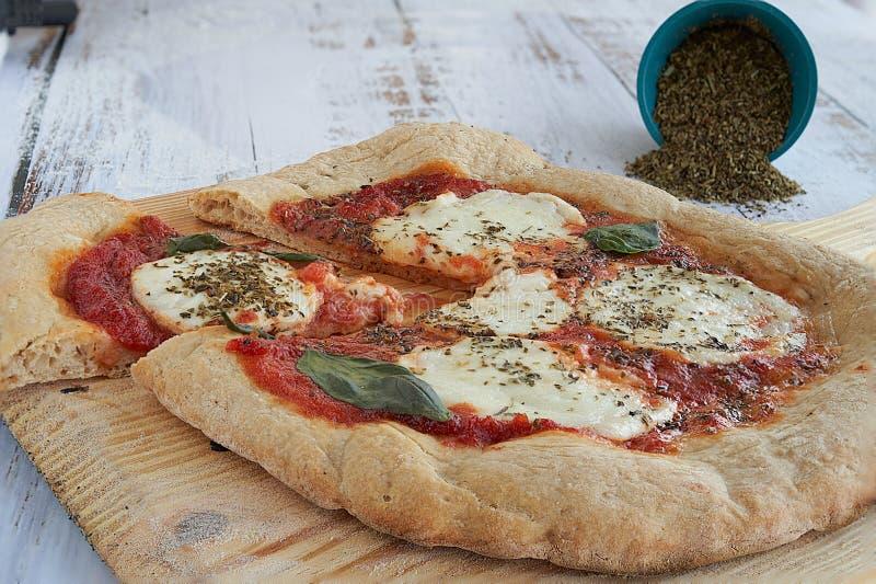 Eigengemaakte pizza met verpletterde verse tomatensaus, mozarellakaas en padano en basilicum royalty-vrije stock afbeelding